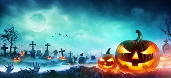 Jack O Lanterns And Zombie Hands Rising Out Of A Graveyard. In Misty Night royalty free stock photography