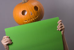 Jack o lataern. Jack-o-lantern at halloween time holding green empty banner royalty free stock image