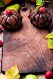Jack-o-linterna alrededor de la tabla de cortar vacía en fondo de madera Concepto del otoño Víspera de Todos los Santos Visión su Imagenes de archivo