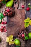 Jack-o-linterna alrededor de la tabla de cortar vacía en fondo de madera Concepto del otoño Víspera de Todos los Santos Visión su Imagen de archivo libre de regalías