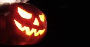 Jack-o-linterna brillante Calabaza de Halloween con humo asustadizo de la cara dentro con la llama aislada en el fondo negro almacen de metraje de vídeo
