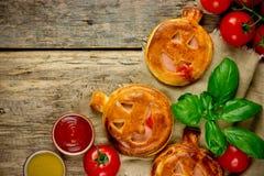 Jack-o& x27; - Pizza del jamón de las verduras de la linterna mini para el partido de Halloween encendido Foto de archivo libre de regalías