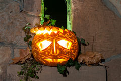 Jack oLantern on Halloween night. By a narrow castle window stock image