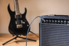 Plugged guitar and amp. Jack plugged guitar and amp close up royalty free stock image