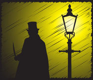 Jack The Ripper Grunged In The Light. A grunged silhouette of jack the ripper with a knife in the light of a street lamp Stock Photography