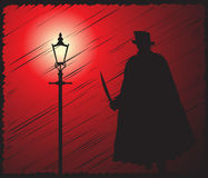 Jack The Ripper In The Light Scribble Grunged. A grunged silhouette of jack the ripper with a knife in the light of a street lamp Royalty Free Stock Images