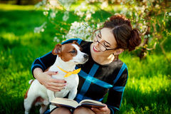 Jack Russell Terrier dog with owner woman playing in the spring outdoors. Modern Youth Lifestyle Concept. Beautiful young brunette woman enjoying in park Stock Photos