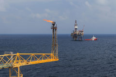Jack up drilling rig, flare boom, and crew boat stock images