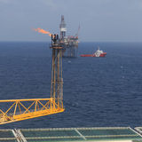 Jack up drilling rig, flare boom, and crew boat Stock Image