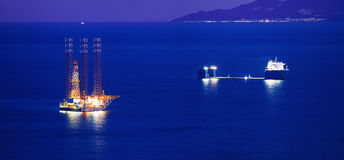 Jack up rig and a cargo ship. A jack up rig and a cargo ship during dusk in the gulf of Kavala, Greece Royalty Free Stock Photography