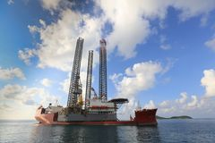 Jack up rig legs Transportation. By heavy lift vessel orange color on the sea with blue sky stock images