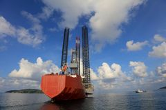 Jack up rig legs Transportation. By heavy lift vessel orange color on the sea with blue sky stock photos