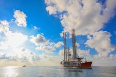 Jack up rig legs Transportation. By heavy lift vessel orange color on the sea with blue sky royalty free stock photo