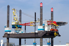 Jack up Rig. ROTTERDAM, THE NETHERLANDS - AUG 1, 2014: Self Elevating Platform JB-118 docked in the Port of Rotterdam. The rig is build in 2013 and owned by stock images