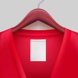 Jacke mit dem Aufkleber, der an einem Aufhänger hängt Stockfotografie