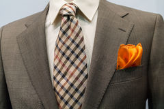 Jacket with brown checkered tie and orange handker. Close-up of light grey checkered jacket with white shirt, brown checkered tie and orange handkerchief Stock Image