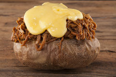 Jacket of potato with pulled pork and melting cheese Royalty Free Stock Images