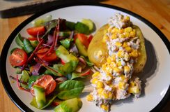 Jacket potato with vegetable salad. Jacket potato with tuna and sweet corn filling and vegetable salad stock photo
