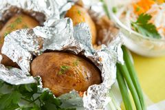 Jacket potatoes cooked in foil, and greens Stock Photos