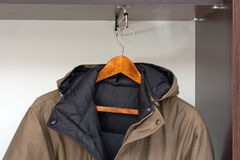 Jacket on the rack. Winter jacket hanging on the rack in the wardrobe Stock Photos