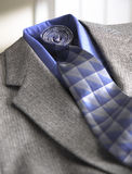 Jacket and Tie. Close-up of a grey mens dress jacket and blue tie. limited depth of field Royalty Free Stock Photo