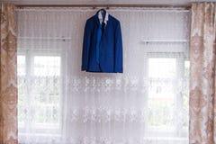 Jacket. Wedding jacket hanging over the window ledge stock images