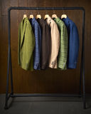 Jackets hanging on a rack with a wooden background Stock Image