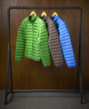 Jackets hanging on a rack with a wooden background Royalty Free Stock Images