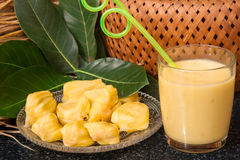 Jackfruit juice in a glass. Fresh sweet jackfruit slices on a glass plate. Stock Images