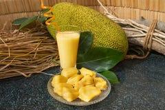 Jackfruitsaft in einem Glas Neue süße Jackfruitscheiben auf einer Glasplatte Lizenzfreie Stockfotografie