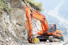 Jackhammer. Large orange jackhammer smashing rocks Stock Images