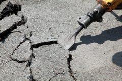 Jackhammer. Close up of asphalt demolishing with pneumatic plugger hammer Stock Image