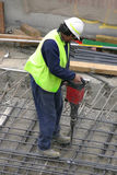 Jackhammer. A workman using a jackhammer.  Focus is to the jackhammer Stock Images