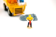 Jackhammer. Toy jackhammer worker in front of dumptruck isolated on a white background Royalty Free Stock Photos
