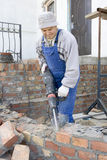 Jackhammer. Builder destroys brick wall a jackhammer Royalty Free Stock Photos