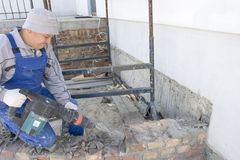 Jackhammer. Builder destroys brick wall a jackhammer Royalty Free Stock Photo