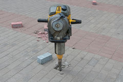 Jackhammer and pavement tiles. Stock Photo