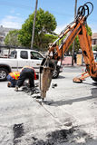 Jackhammer Street Repair. Jackhammer machine tearing up city street with maintenance workers in the background Stock Photography