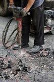 Jackhammering gata för arbetare Arkivbild