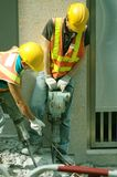 Jackhammers. Construction workers operating jackhammers breaking up concrete Stock Image