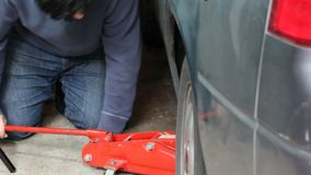 Jacking up a car in a garage. Using jack to prep for changing a tire stock video footage