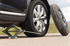 Jacking up a car to change a tyre. After a roadside puncture with the hydraulic jack inserted under the bodywork raising the vehicle and the spare wheel royalty free stock images