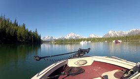 Jackson Lake at Teton mountains. The Jackson Lake, Wyoming, seen from a boat with the Tetons in the background. A few other boats on the water. It is late Spring stock footage