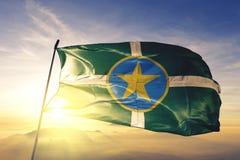 Jackson-Stadthauptstadt von Mississippi des Flaggentextilstoffgewebes Vereinigter Staaten, das auf den Spitzensonnenaufgangnebeln stockfotos