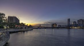 JACKSONVILLE FL, ZONSONDERGANG HOOFDst BRUG RIVERWALK DE STAD IN stock foto