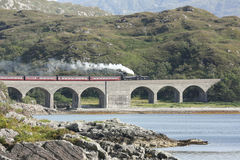 Jacobite steam train crossing Loch nan umbh viaduct, Scotland, UK. Stock Images