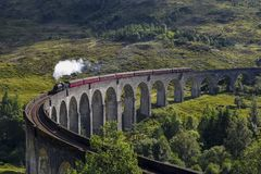 Jacobite steam train on Glenfinnan Viaduct approaching, Highlands, Scotland, UK. Nostalgic steam train on the way from Fort William to Mallaig - Hogwarts Stock Image