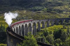 Jacobite steam train on Glenfinnan Viaduct at Loch Shiel, Mallaig, Highlands, Scotland. Old train on a viaduct with white steam Royalty Free Stock Photography