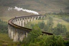 Jacobite steam train, a.k.a. Hogwarts Express, passes Glenfinnan. Jacobite steam train, a.k.a. Hogwarts Express, passes  on a cludy day Royalty Free Stock Photo