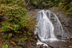Jacobs Falls in Autumn, waterfall in northern Michigan, USA. Cascading water flows rapidly over Jacob's Falls near Eagle River Michigan. Autumn colors and rock Royalty Free Stock Photography